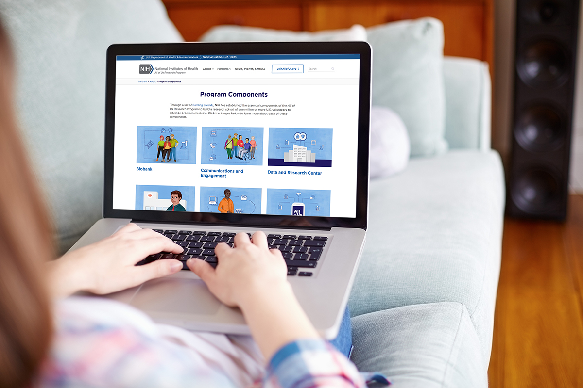 A person on a couch using a laptop computer on which the Program Components webpage on the NIH All of Us Research Program website is visible.