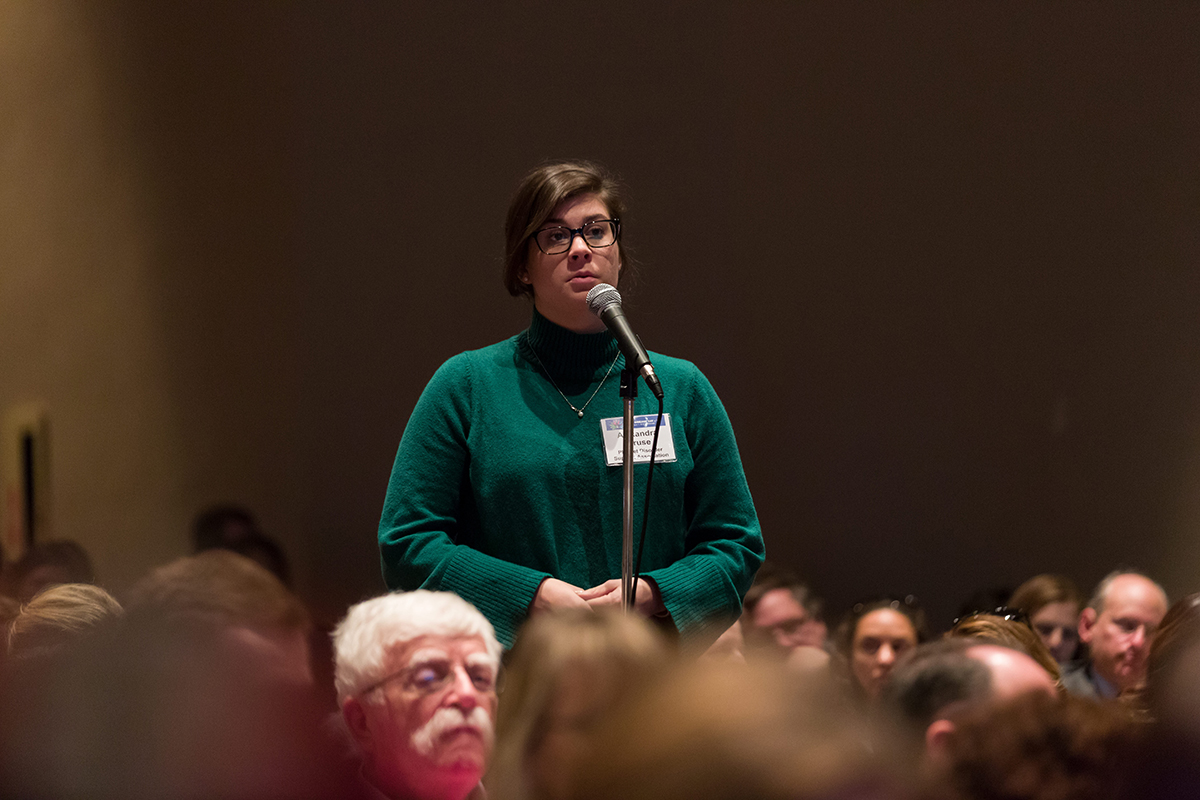 An event participant standing at a microphone in the audience to ask a question.